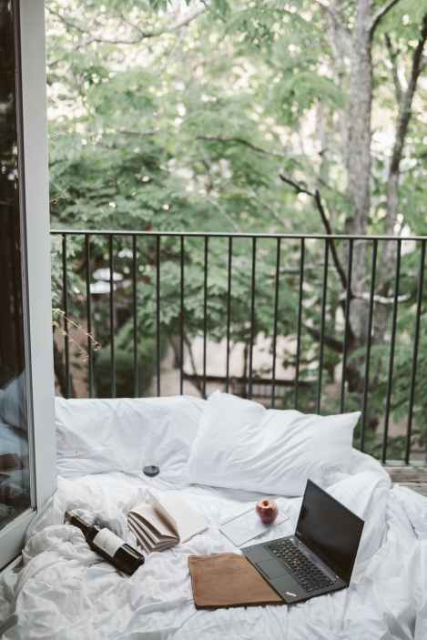 laptop on bed near the balcony